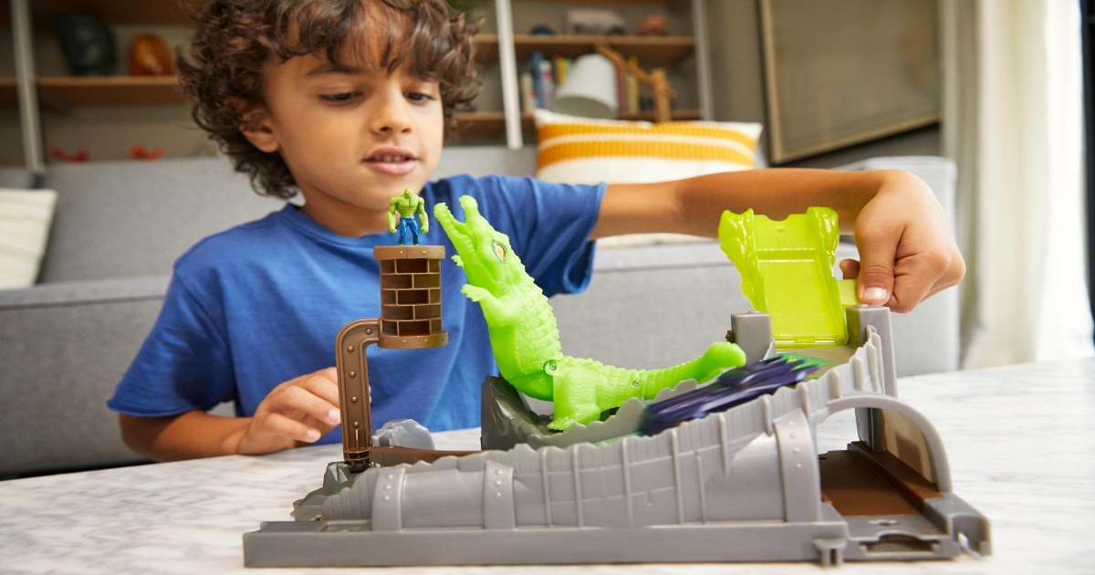 Boy playing with a hot wheels playset