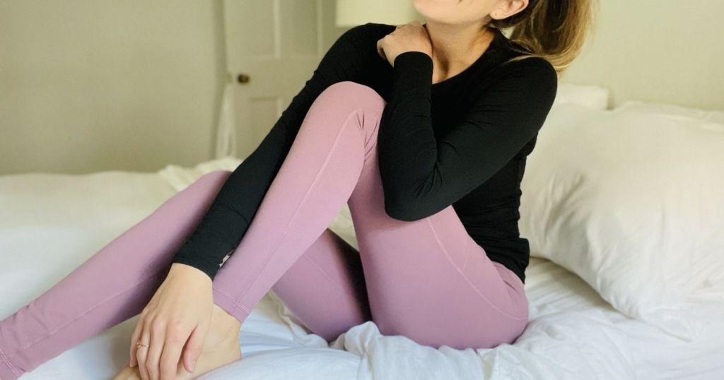 woman sitting on bed wearing black top and pink leggings