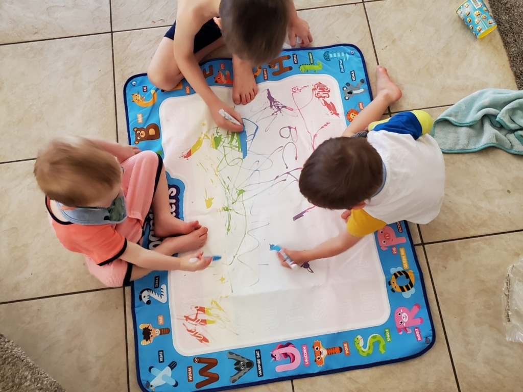 kids drawing on a water doodle at