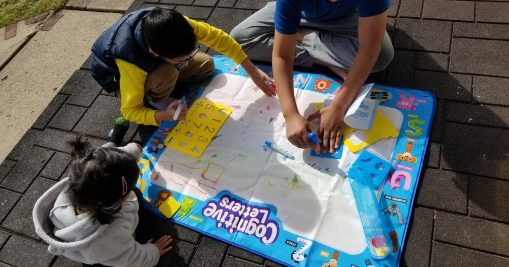 kids coloring outside on a water doodle mat