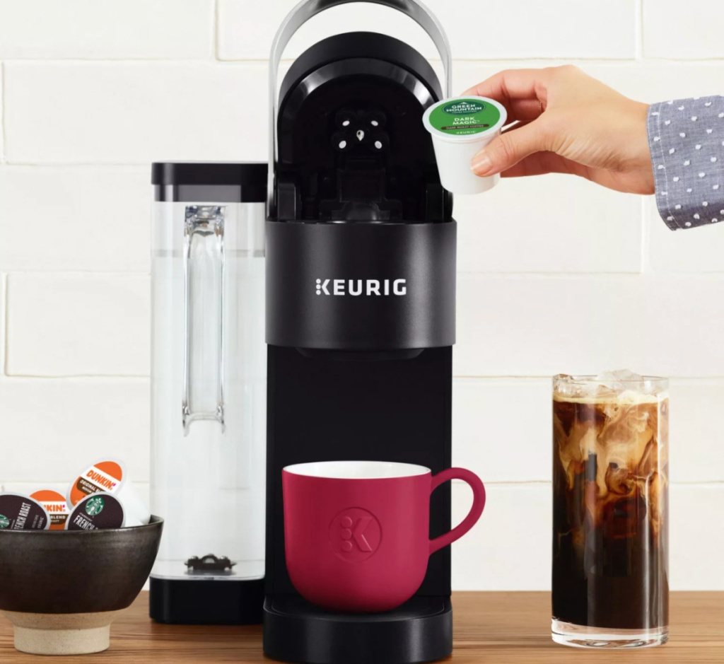 hand putting k cup into keurig