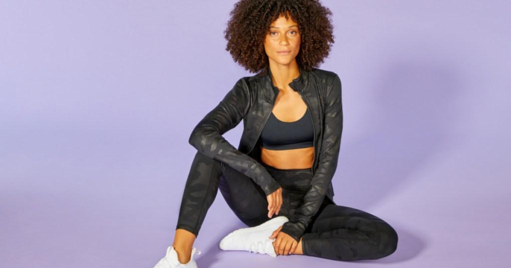 woman wearing black leggings. sports bra and jacket