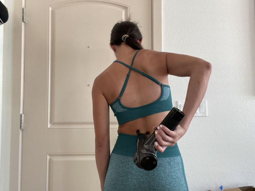 woman using back massager on back