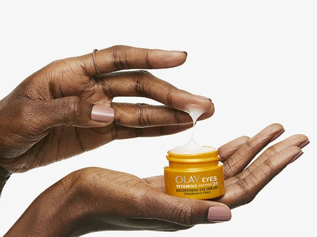 hand holding jar of Olay Brightening Cream