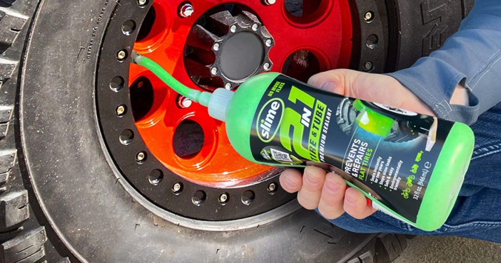 man squeezing a bottle of slime tire and tube sealant