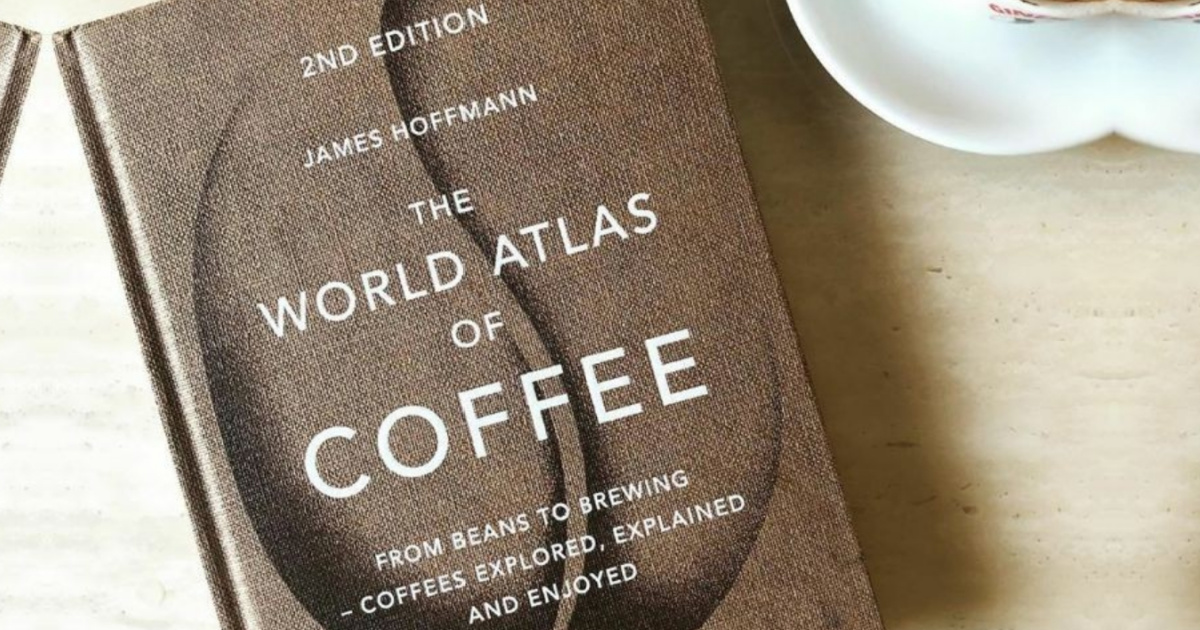 world atlas of coffee book cover next to coffee cup