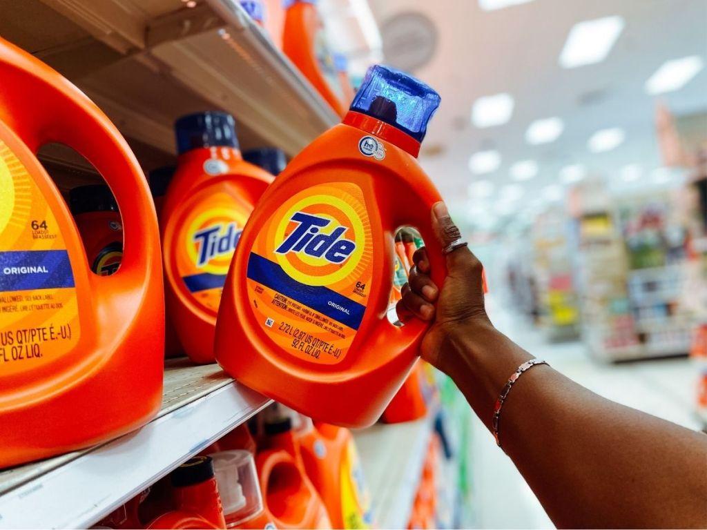 hand pulling Tide detergent off shelf