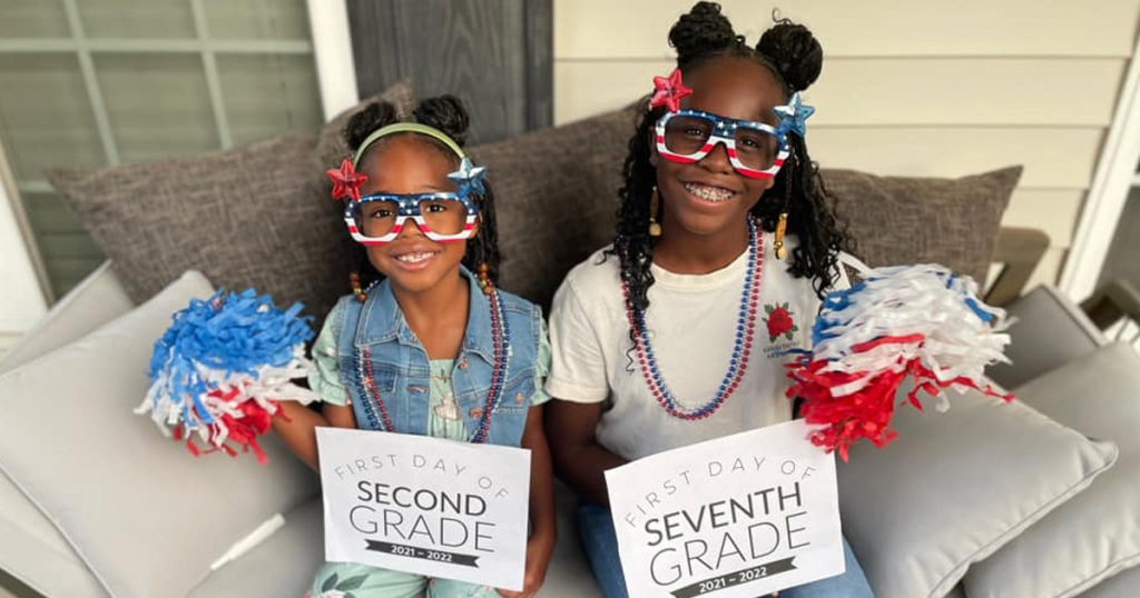 two adorable girls with back to school signs