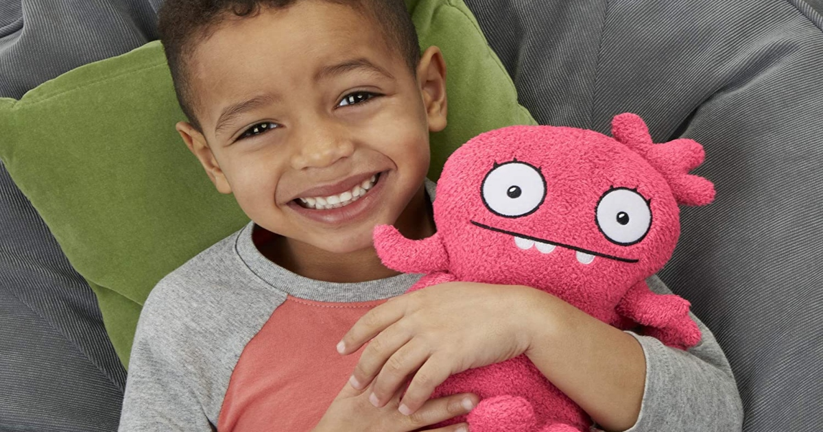 boy in a soft chair with a green pillow holding a pink plush uglydoll