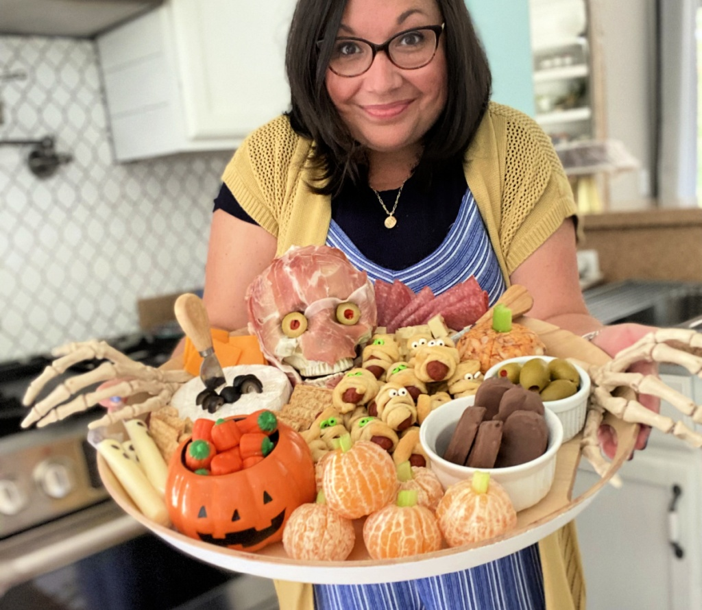 woman holding a halloween snack board