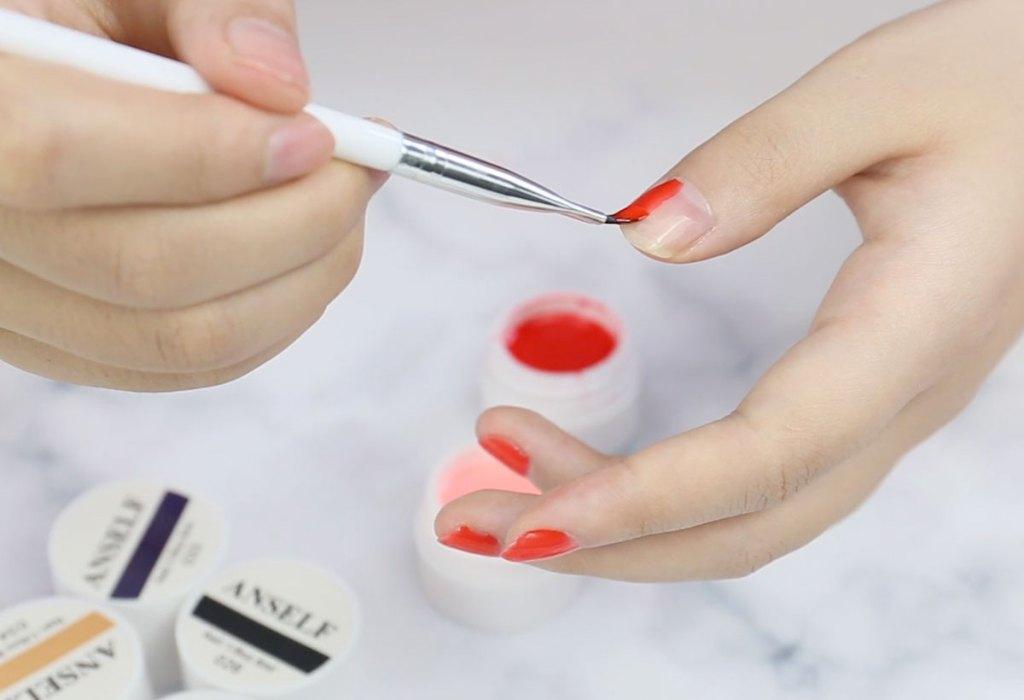 woman applying red polish to nails