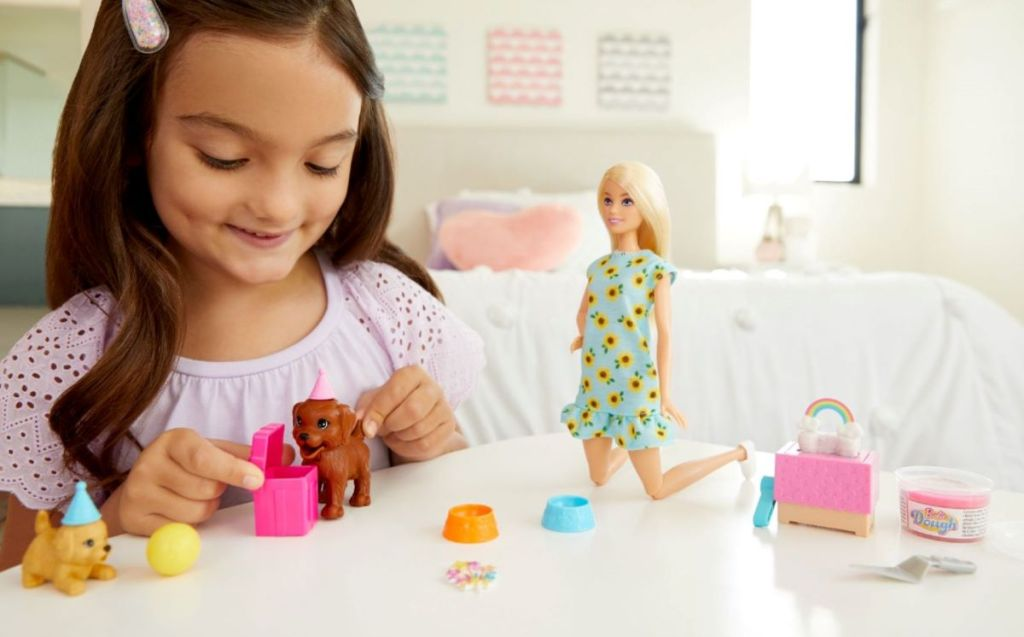 girl playing with Barbie's