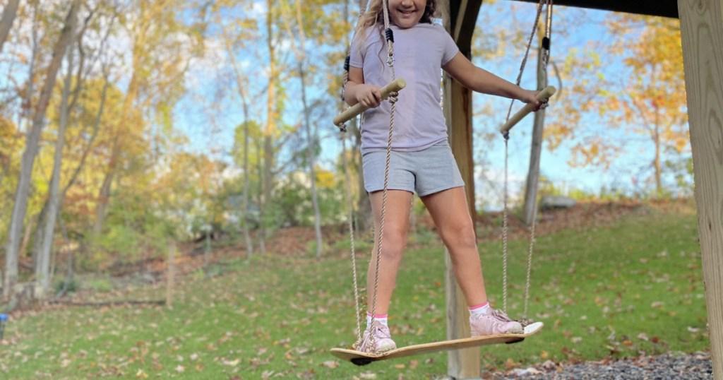 girl on a wooden skateboard swing