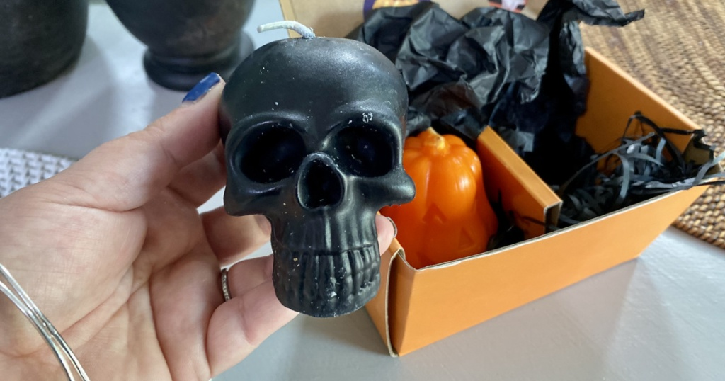 woman holding a black skull candle