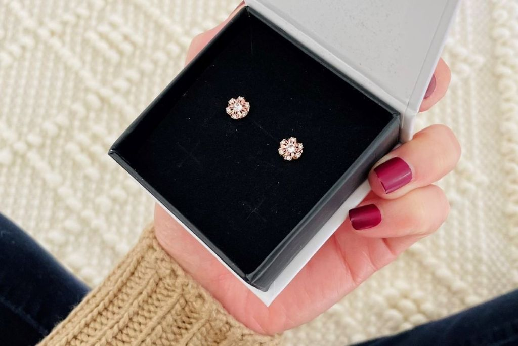 hand holding a box of earrings