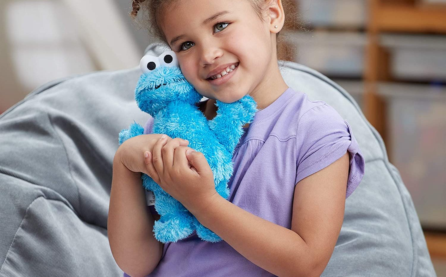 small girl cuddling Cookie Monster