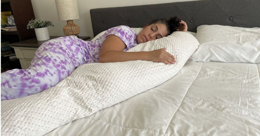 woman laying on a bed with a body pillow