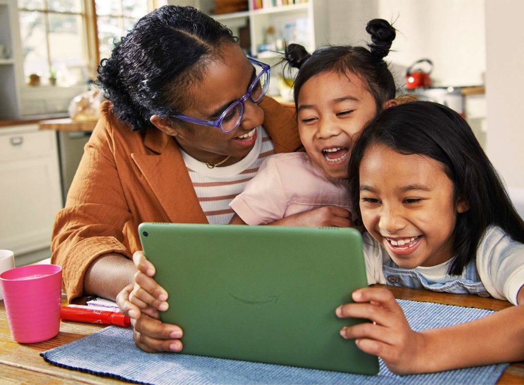 woman and two kids looking at green fire tablet