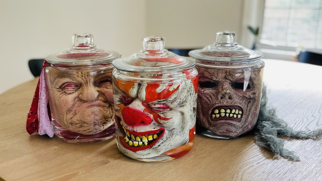 creepy halloween face masks in clear glass jars on wood table
