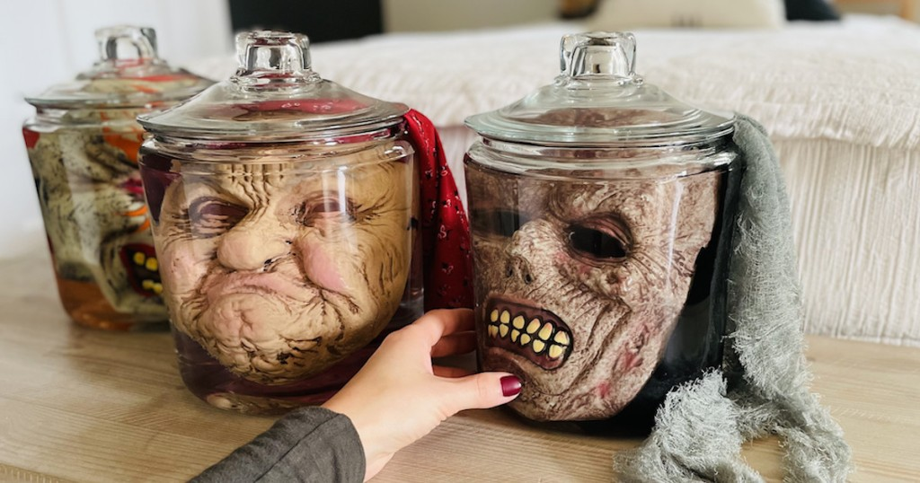 hand holding side of glass jar with creep halloween face masks in jar