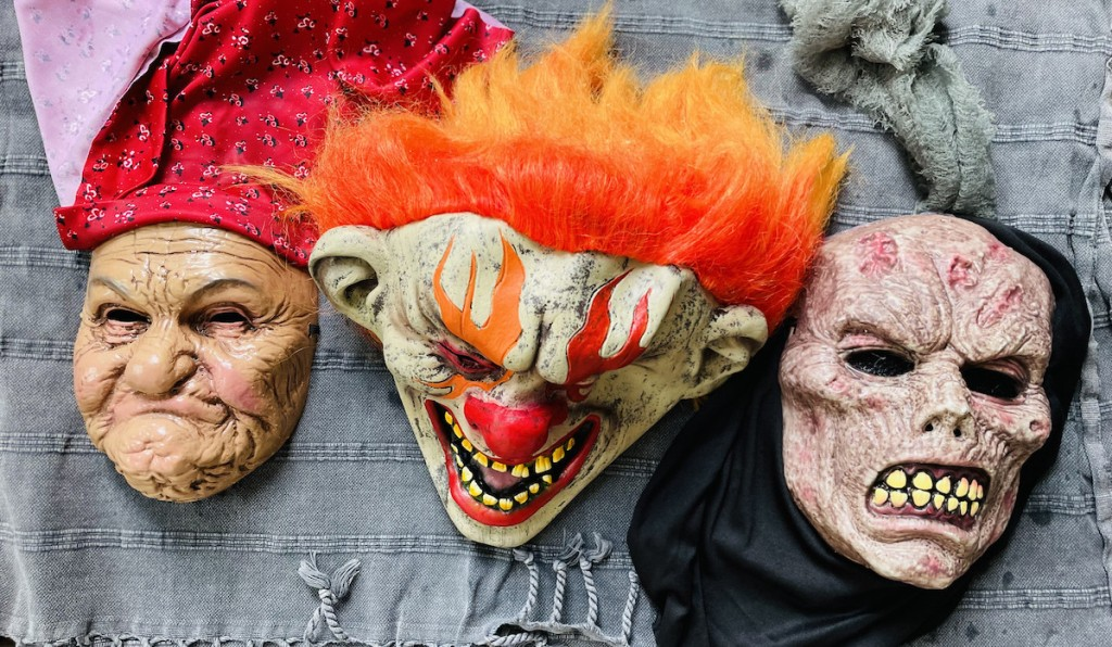 creepy halloween masks laying out to dry on blue towel