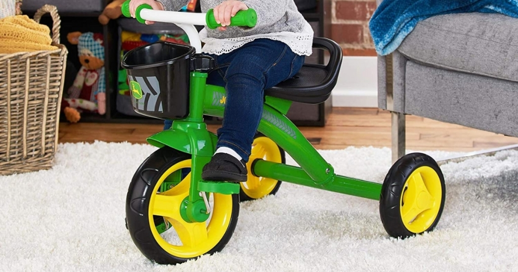 young girl riding john deere pedal tricycle