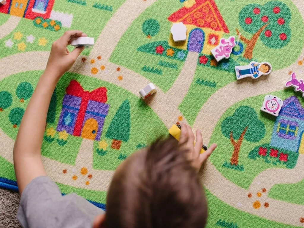 boy playing with melissa & doug blues clues activity rug