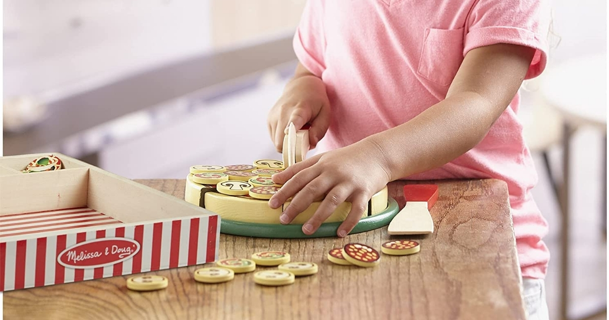 girl playing with melissa and doug wooden pizza play set