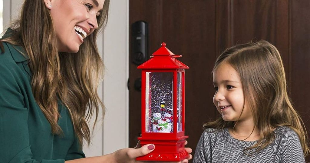 woman holding a snow globe next to a little girl