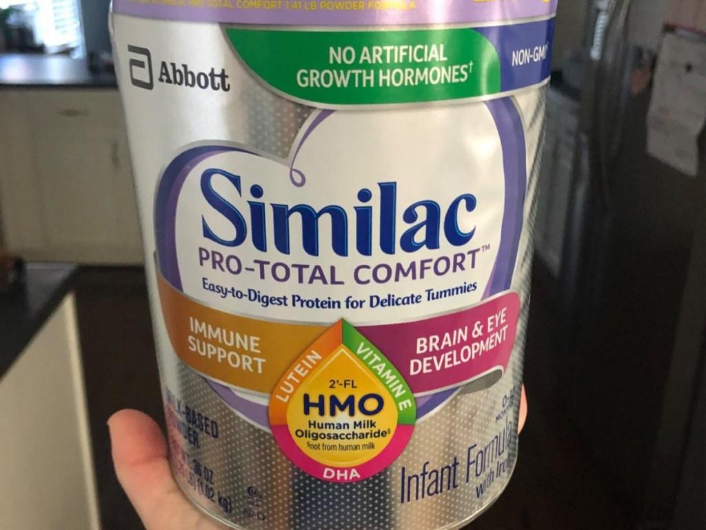 hand holding large canister of infant formula