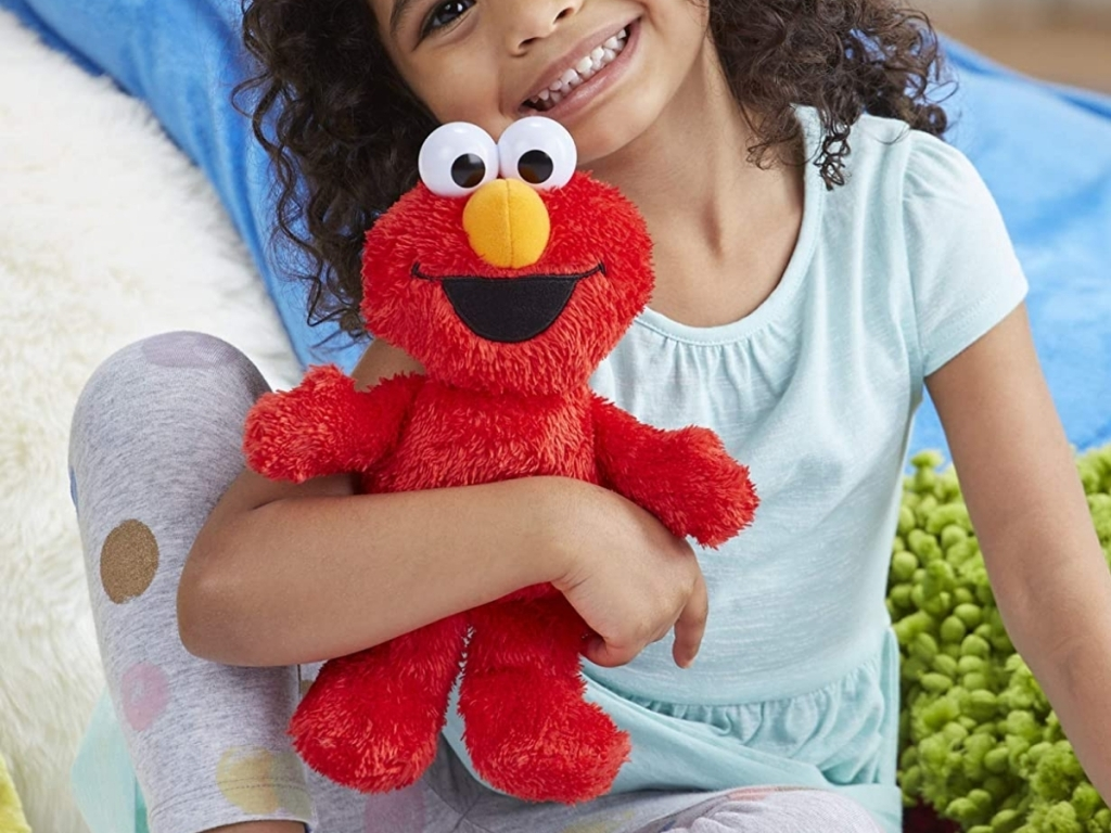 little girl with tickle me elmo toy