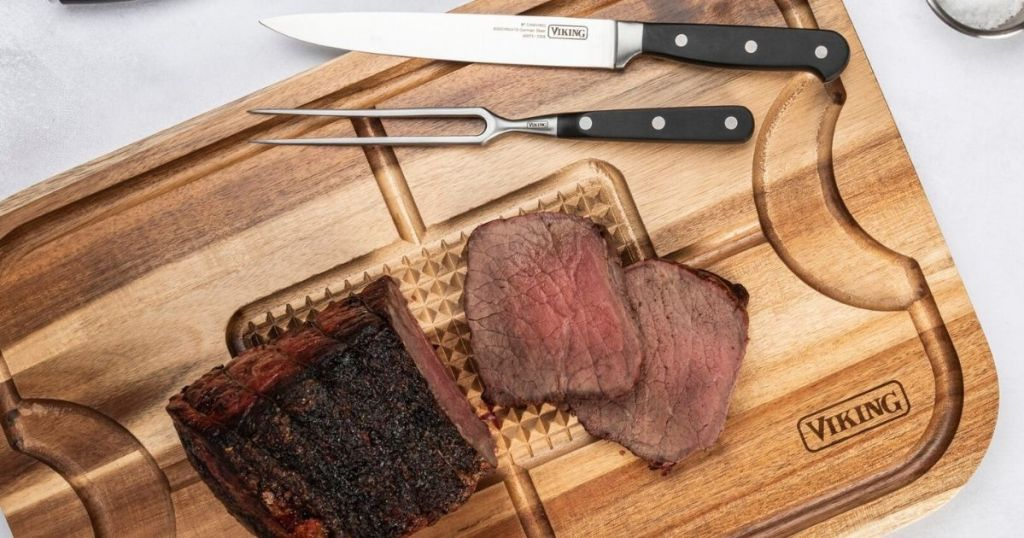 cutting board with meat and knives on it