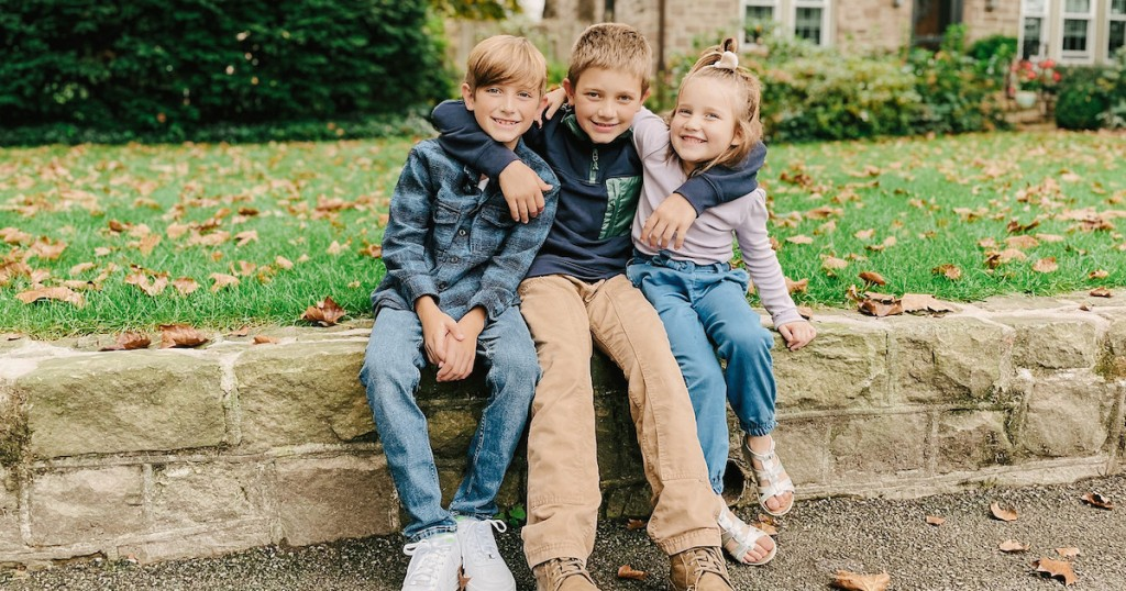 three kids sitting on stone wall outside of house