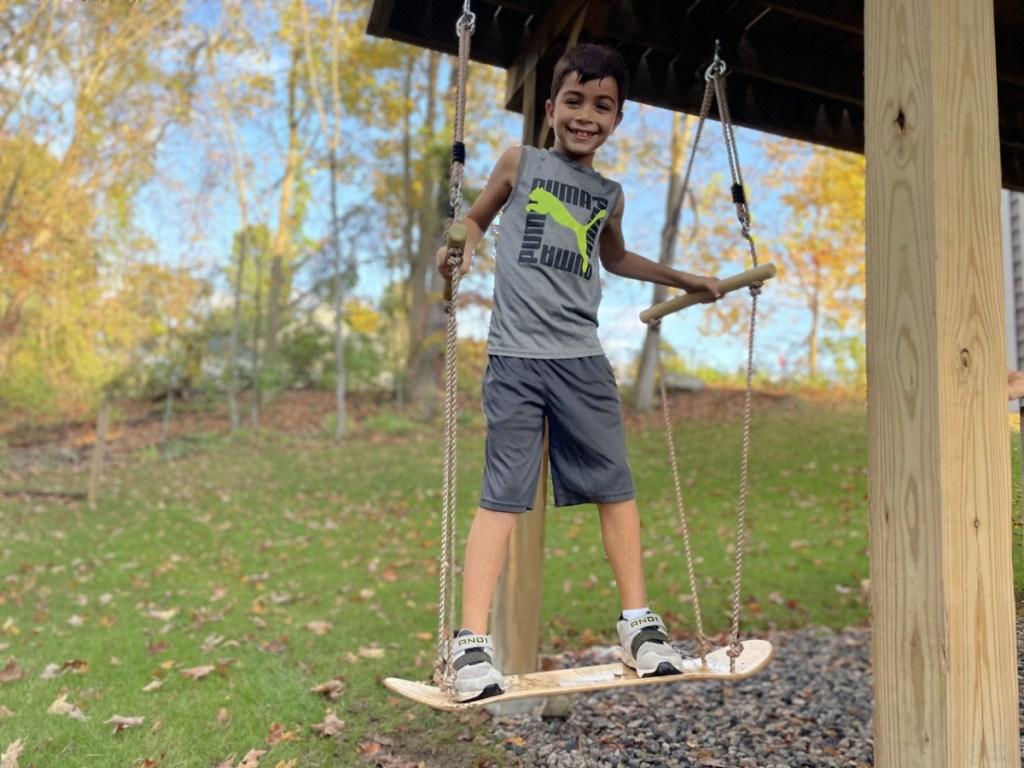 boy on a wooden skateboard swing