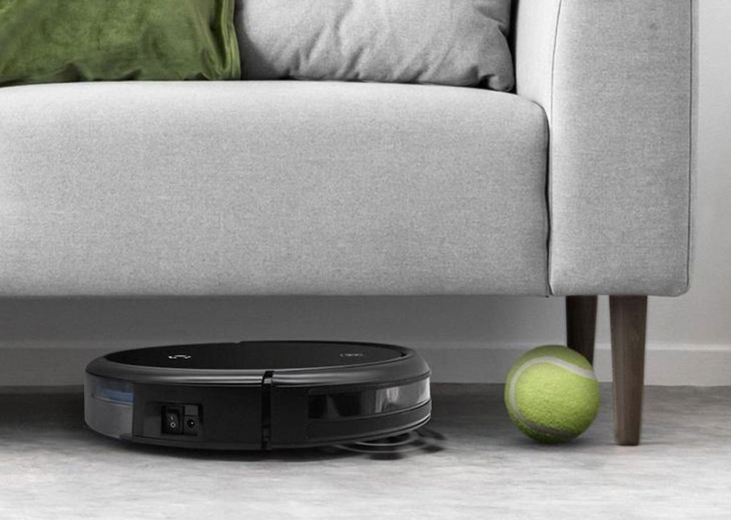 black robot vacuum under couch next to tennis ball