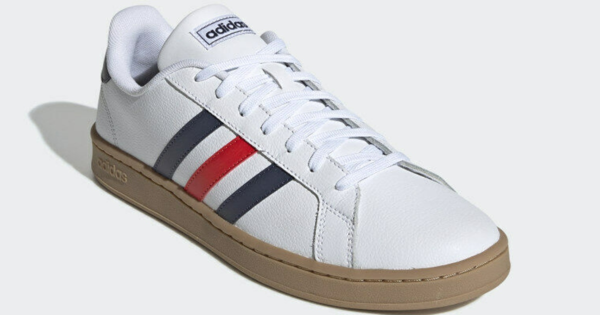a white adidas shoe with three colored stripes
