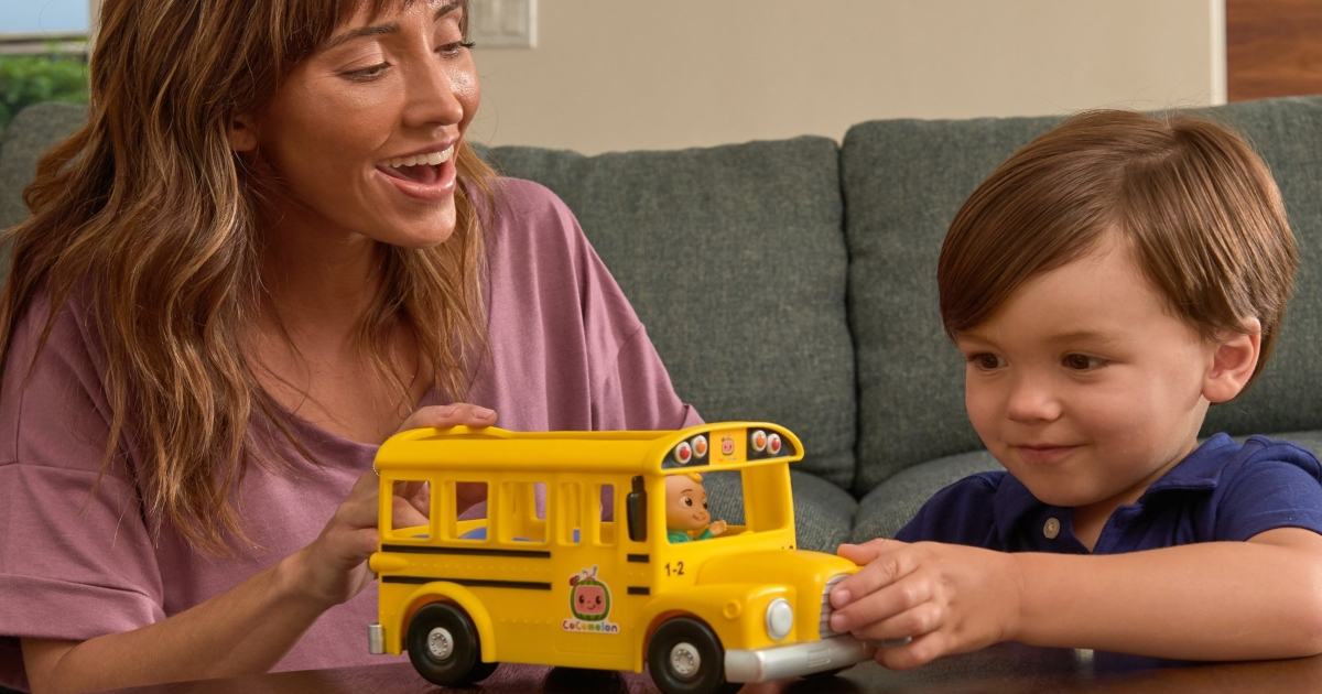 boy playing with Cocomelon school bus on a table with his mom
