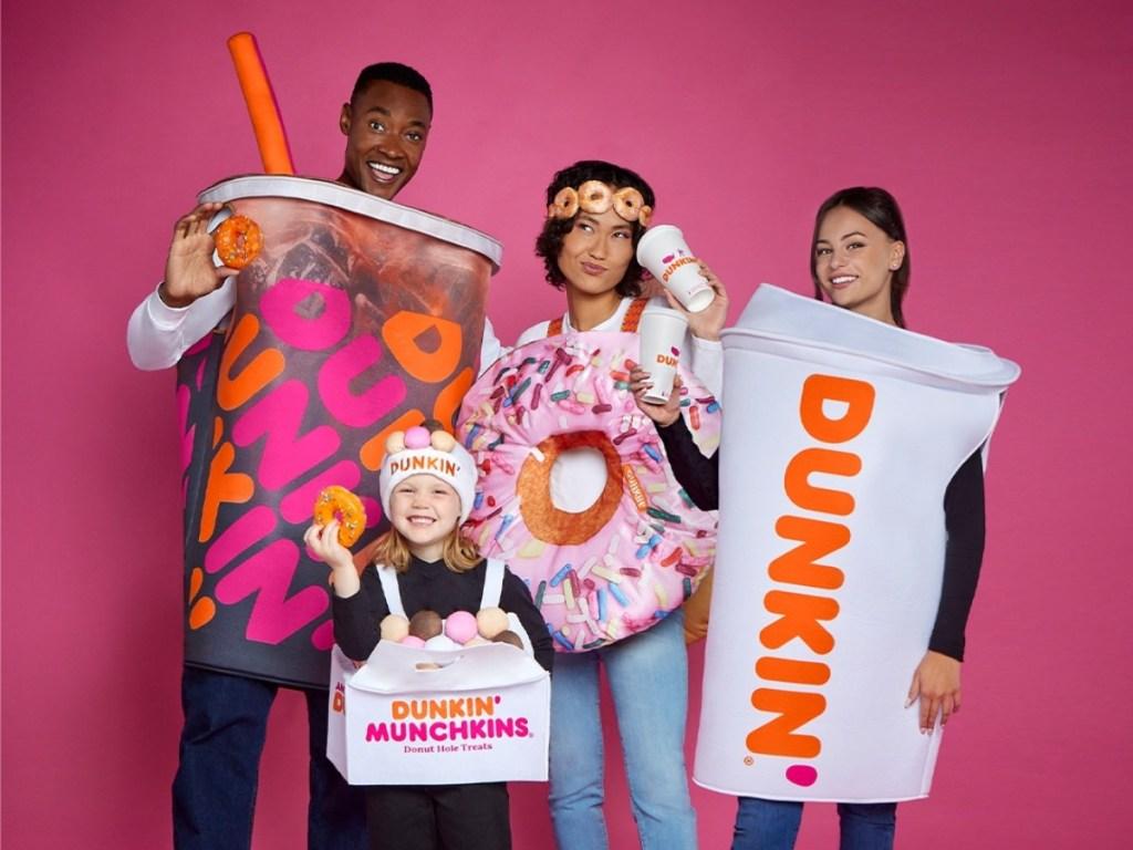 4 people wearing Dunkin' Halloween costumes