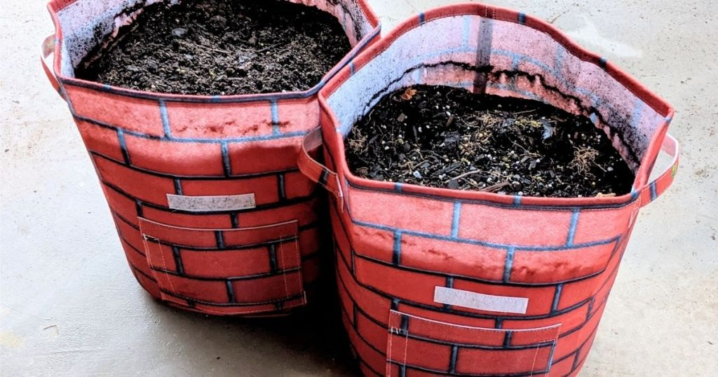 2 garden grow bags filled with soil
