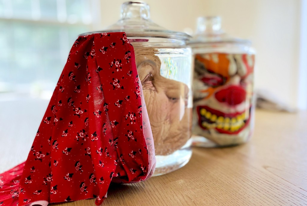 close up of halloween masks in glass jars on wood table