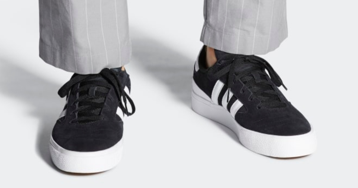 picture of a man's fee wearing black Adidas sneakers with white lines on the sides