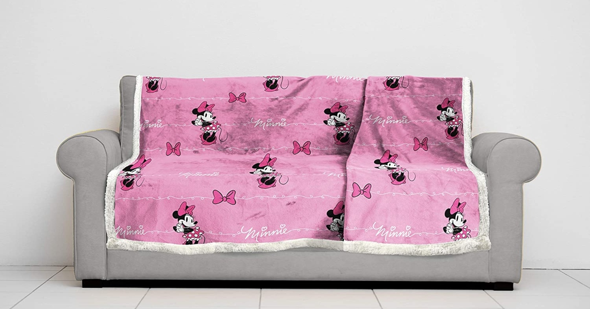Pink Minnie Mouse Sherpa blanket layed out on a couch