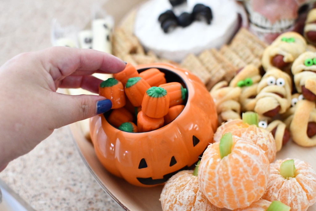 pulling out a pumpkin candy from Halloween snack board
