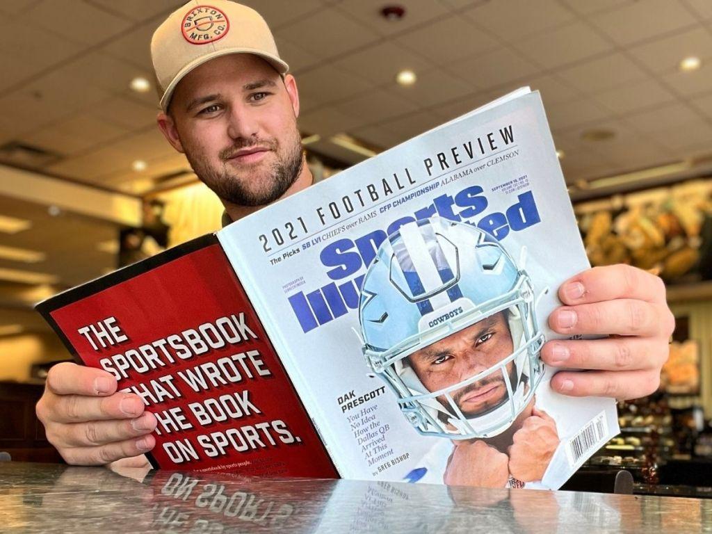 man reading Sports Illustrated magazine