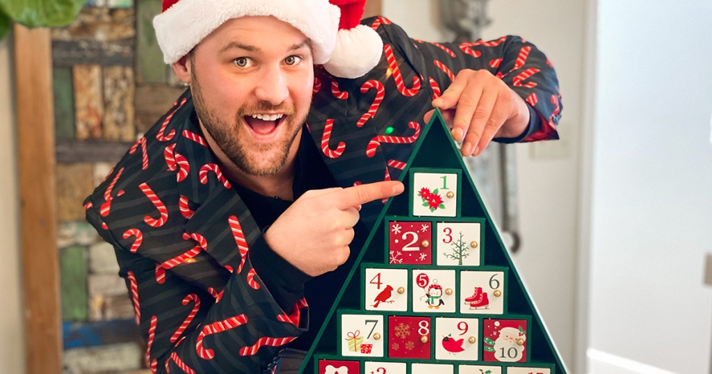 man wearing christmas jacket pointing to advent calendar