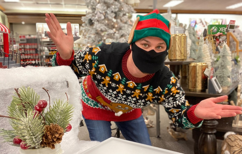 man in christmas sweater shopping in store