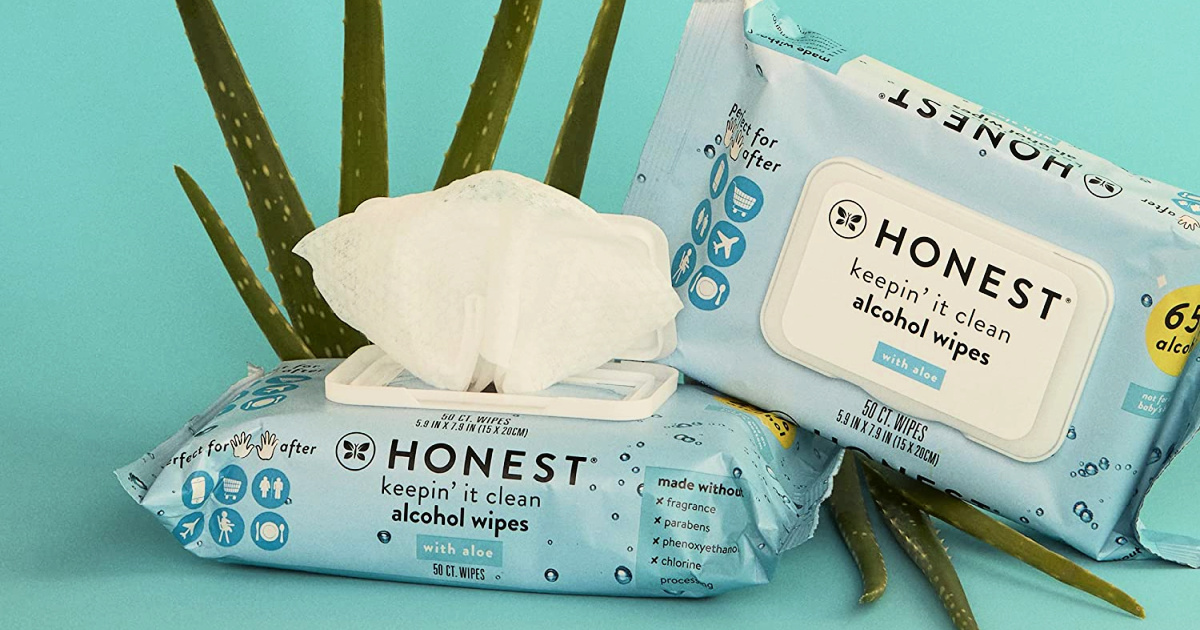 packages of alcohol wipes both open and closed in front of a spray of aloe plant