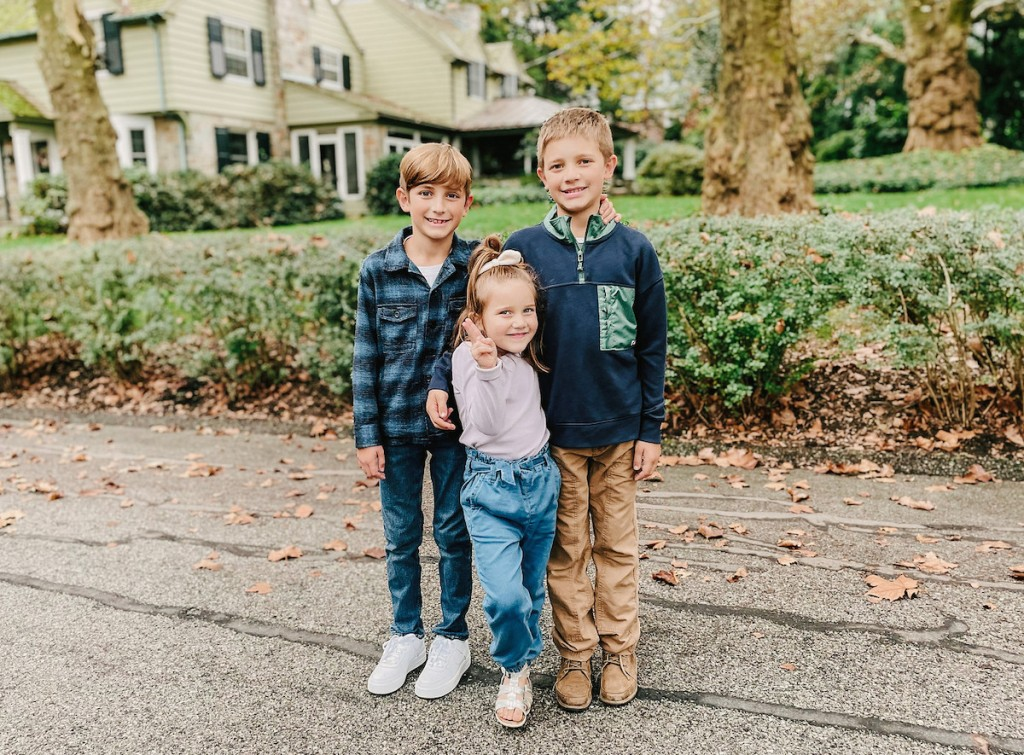 three kids standing together in street
