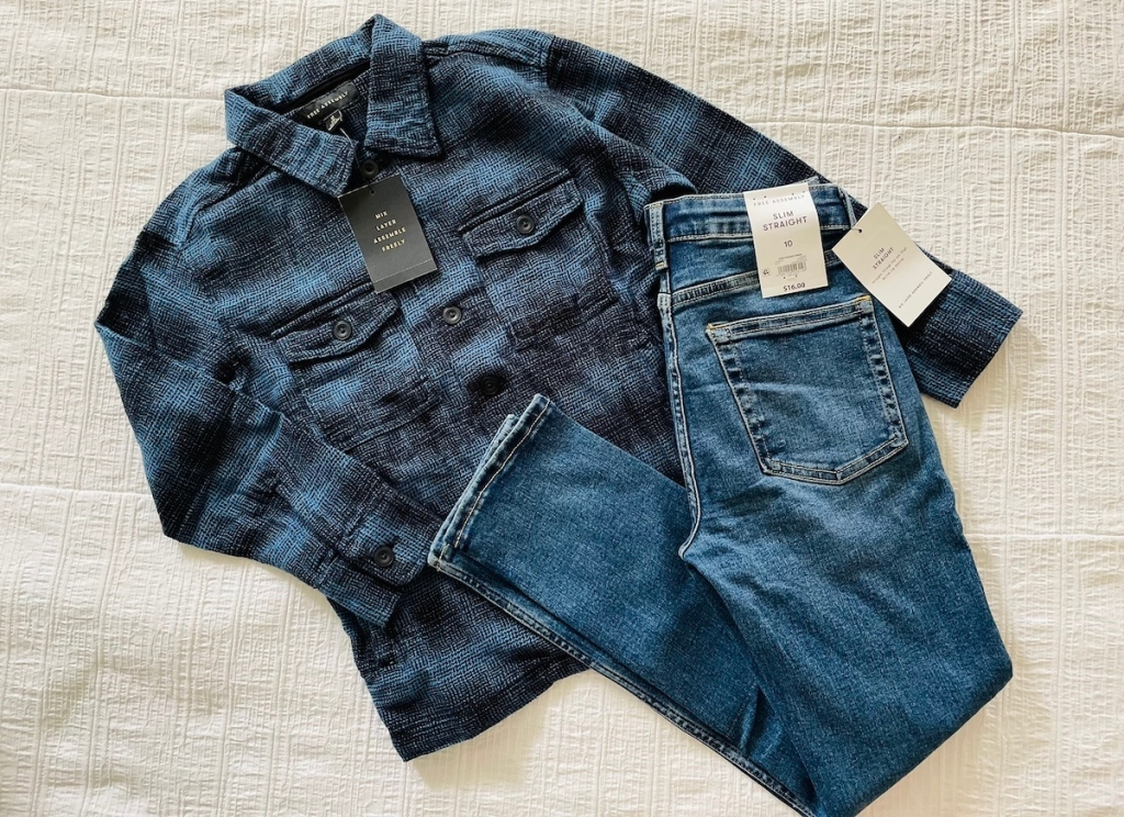 blue and black flannel and jeans laying on white bed