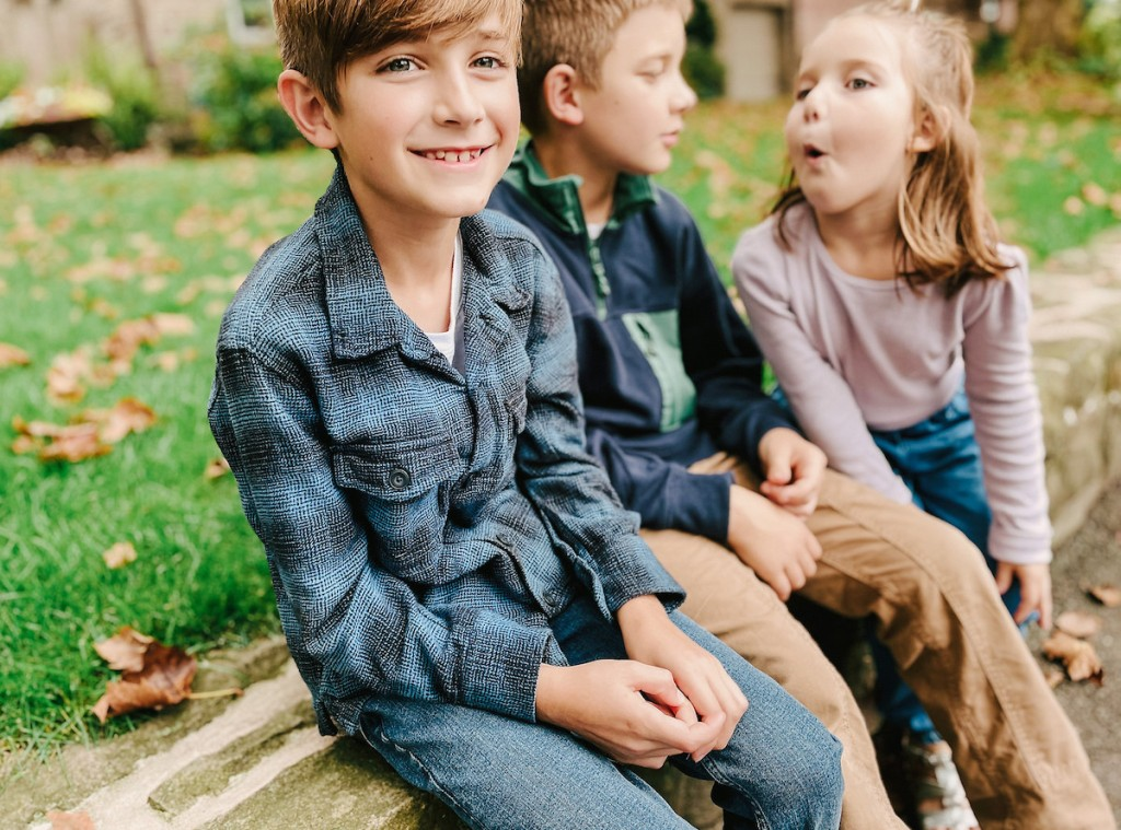 close up of boys smiling on stone wall with kids
